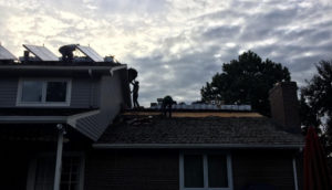 Residential roof repair company repairing hail damage