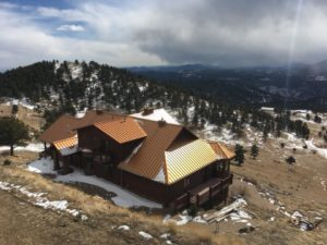 Commercial Roofing Company installed flashing on metal roofing house overlooking Rocky Mountains