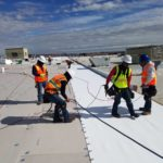 men working on roof repair and replacement