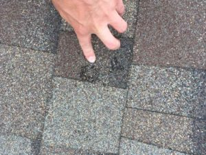Two spot hail damage on grey roof insurance claim